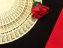 Wooden fan. Carved wooden japanese fan with a red rose on red and black velvet cloth Stock Images