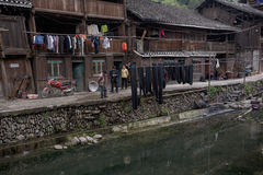 Wooden farmhouses Chinese peasants are located on banks river vi Stock Photos