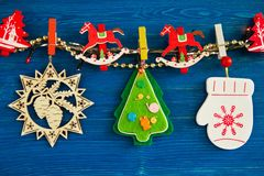 Colorful Christmas decorations and Christmas lights on a rope on the blue wooden background. Royalty Free Stock Photo