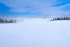 Wooden fence. Old wooden fence covered with snow under blue sky Royalty Free Stock Photography