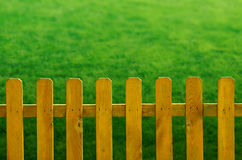 Wooden Fence. Yellow wooden fence over a green grass background royalty free stock photography