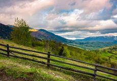 Wooden fence across the hill. Beautiful agriculture scenery of Carpathian mountains on a cloudy springtime day royalty free stock images