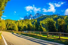 Wooden fence. Along the asphalt road. Summer sunset. Magnificent serrated cliffs of Dolomites, Tirol.  The concept of eco-tourism stock photos