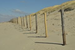 Wooden fence along the beach and dunes. royalty free stock photography