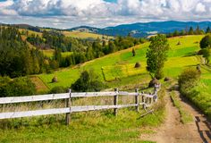 Wooden fence along the country road. Haystacks on agricultural fields. rolling hills ends up with mountain ridge in the distance. beautiful sunny day under the Stock Image