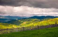 Wooden fence along the grassy hillside. Beautiful springtime landscape of Carpathian mountains on a cloudy day Royalty Free Stock Photo