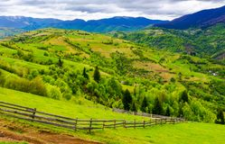 Wooden fence along the grassy hillside. Beautiful springtime landscape of Carpathian mountains on a cloudy day Stock Images