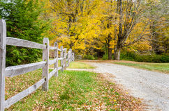 Wooden Fence along a Gravel Road to the Woods Royalty Free Stock Photography