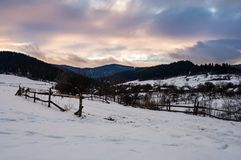 Wooden fence along the snowy road. Beautiful winter landscape of mountainous rural area at cloudy sunset Royalty Free Stock Photography