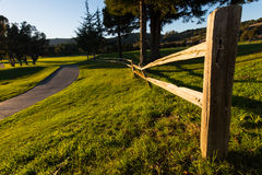 Wooden fence along a walking path with grass Stock Image
