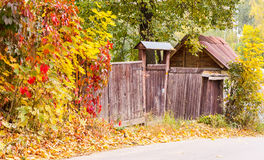 Wooden fence in autumn. Wooden fence surrounded by yellow and red leaves in autumn Royalty Free Stock Photo