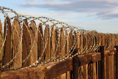 A wooden fence with barbwire Stock Photos