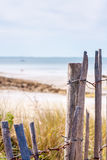 Wooden fence on beach. A weathered wooden fence on a beach Royalty Free Stock Photo