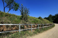 Wooden fence bordering dirt road. SAO ROQUE, SP, BRAZIL - AUGUST 22, 2015 - Wooden fence bordering dirt road in country area Stock Images
