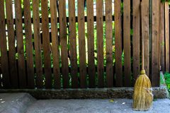 Wooden fence and broom. Rural wooden fence and a straw broom stock photo
