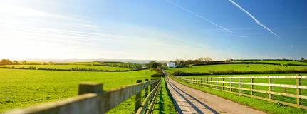 Fence casting shadows on a road leading to small house between scenic Cornish fields under blue sky, Cornwall, England Royalty Free Stock Images