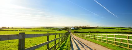 Fence casting shadows on a road leading to small house between scenic Cornish fields under blue sky, Cornwall, England Royalty Free Stock Image