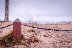 Wooden fence with chain. Fence made of posts of wood with metal chain Royalty Free Stock Photo