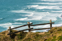 Wooden fence on a cliff by the Pacific Ocean Stock Image