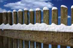 Wooden fence covered with snow before cloudy blue sky Royalty Free Stock Photos