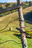 Wooden fence details wrapped by a wire. Simple rural style object on grassy background Royalty Free Stock Photography