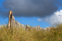 Wooden fence on the dunes with vivid clouded sky Stock Photo
