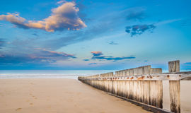 Wooden fence on empty beach at sunset Stock Photo