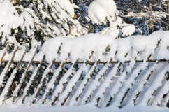 Wooden fence filled up by a snow in a countryside. Stock Photo