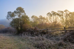 Wooden fence in fog on frozen meadow at sunrize Royalty Free Stock Images