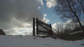 Wooden Fence Gate In Winter. Fence Gate On Green Field Covered With Snow On A Late Winter Afternoon. Blue Skies With Moderate White And Grey Clouds In Time Lapse stock video