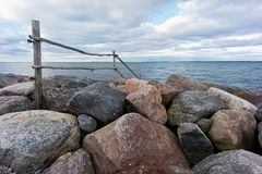 Wooden fence. Goes into the sea over the rocks, natural environment Stock Image