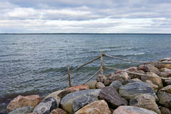 Wooden fence. Goes into the sea over the rocks, nature environment Royalty Free Stock Image