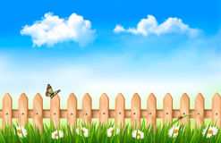 Wooden fence in grass with flowers. And a butterfly. Vector Stock Images