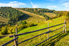 Wooden fence in the grass on the hillside. Near the village Stock Photos