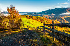 Wooden fence in the grass on the hillside. Near the village Royalty Free Stock Images