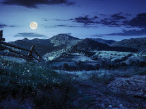 Wooden fence in the grass on the hillside at night. Wooden fence in the grass on the hillside near the village at night in full moon light Royalty Free Stock Image