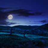Wooden fence in the grass on the hillside at night. Wooden fence in the grass on the hillside near the village at night in moon light Stock Images