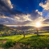 Wooden fence in the grass on the hillside at sunset. Wooden fence in the grass on the hillside near the village at sunset Stock Photography