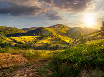 Wooden fence in the grass on the hillside at sunset. Wooden fence in the grass on the hillside near the village in evening light Stock Photos