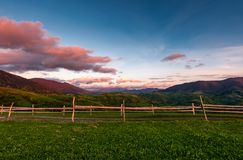 Wooden fence on a grassy hill at sunset. Beautiful rural scenery with reddish clouds over the mountain ridge Stock Photos