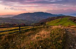 Wooden fence on a grassy hillside at autumn dawn Stock Photos