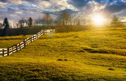 Fence on grassy hillside in autumn at sunset. Wooden fence on grassy hillside in autumn. wonderful rural scenery in fine weather with cloudy sky at sunset Royalty Free Stock Image