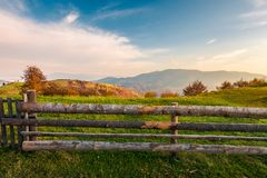 Wooden fence on grassy rural field. Distant mountain in morning haze. lovely autumn countryside stock photo