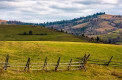 Wooden fence on grassy rural hill in late autumn. Sunny day. beautiful scenery in mountainous area royalty free stock images