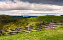 Wooden fence on a grassy slope of Carpathian alps. Beautiful view of rural fields on hills. mountain ridge with snowy tops in the distance. lovely countryside Royalty Free Stock Photos