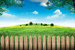 Wooden fence in green field and blue sky with clouds Royalty Free Stock Image