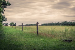 Wooden fence on a green field Stock Photos