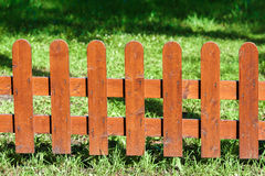 Wooden fence on green grass under the sun Stock Photography