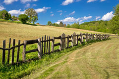 Wooden fence in green landscape. Under blue sky Stock Photography