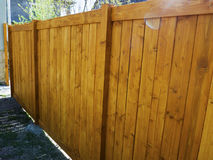 Wooden fence with green lawn and trees Royalty Free Stock Photo
